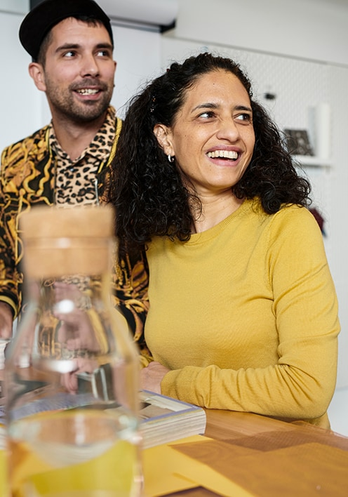 Une femme et un homme assis côte à côte à une table à manger avec une carafe d'eau au premier plan
