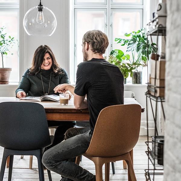 Une femme et un homme assis face à face à une table de salle à manger
