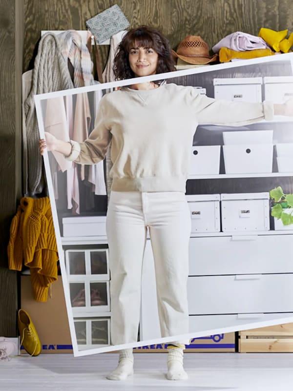 Une femme habillée en blanc se tient devant des étagères désordonnées et tient une grande image des étagères quand elles étaient rangées.