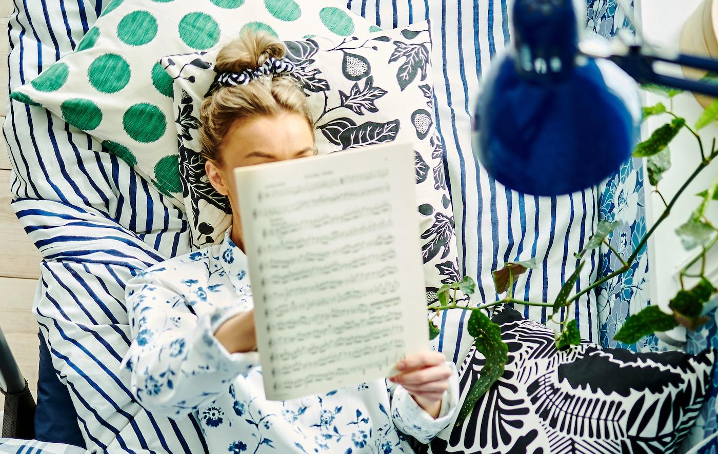 Une femme lit ses partitions bien assise dans un lit, entourée de coussins et de literie, et l'on voit du papier peint à motifs variés sur unmur.