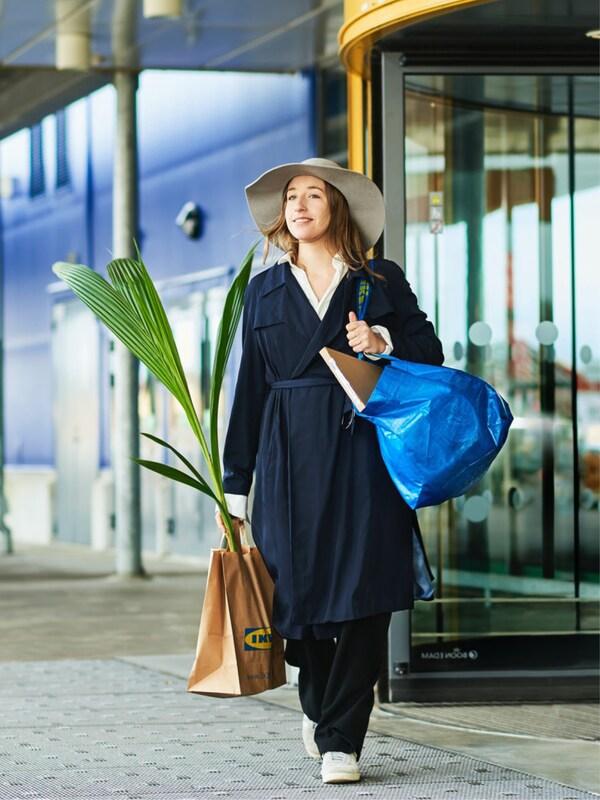 Une femme portant un chapeau de soleil, un long manteau sombre, un sac FRAKTA d'IKEA et un sac en papier d'IKEA avec un palmier quitte la porte tournante de la sortie IKEA en souriant.