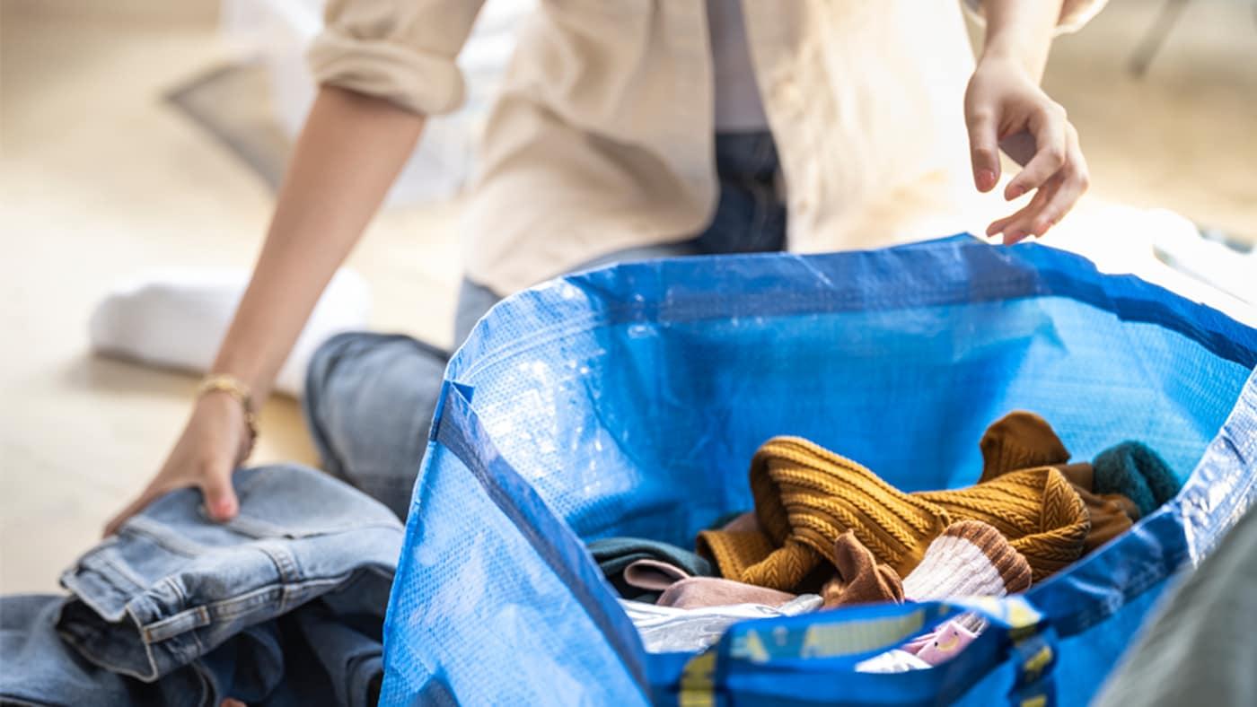 Une femme portant une chemise aux manches retroussées plie des vêtements et les place dans un grand sac bleu IKEA posé sur le sol.