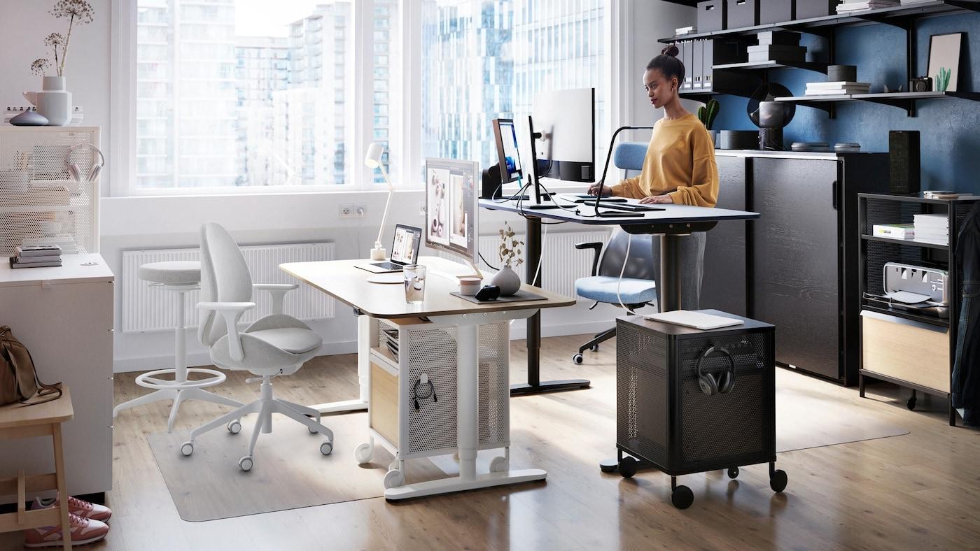 Une femme qui travaille à un bureau assis-debout BEKANT, près d'une grande fenêtre, avec des étagères qui contiennent des dossiers sur le mur derrière elle.