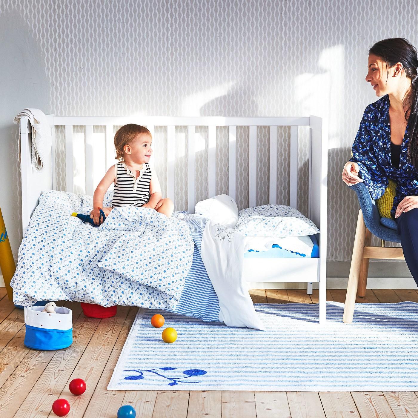 Une femme regarde un bébé assis sur un lit avec des textiles bébé GULSPARV bleus et blancs. Par terre, un tapis GULSPARV à rayures.
