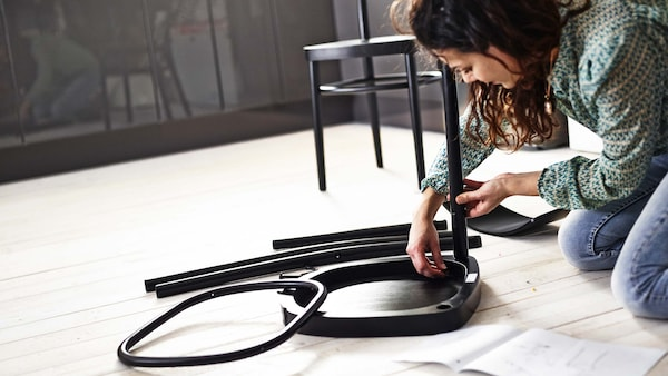 Une femme s'assied sur le sol et assemble une chaise. Devant elle se trouvent les différentes pièces et les instructions de montage.