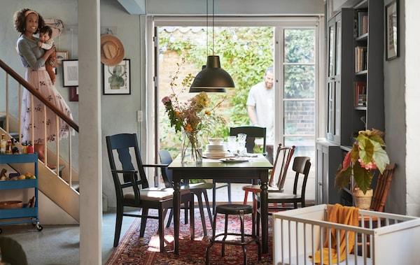 Une femme tenant un bébé descendant les escaliers pour arriver dans la salle à manger équipée de tables et de chaises, avec des portes donnant sur un jardin.