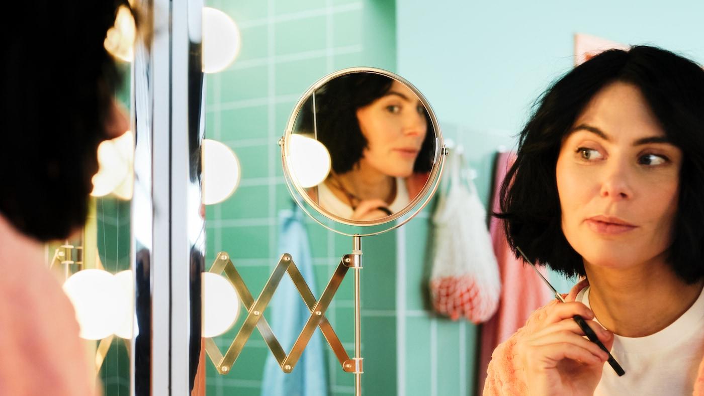 Une femme tenant une paire de ciseaux se regarde dans un miroir FRÄCK à bras extensible pendant qu'elle se coupe les cheveux dans une salle de bain verte.