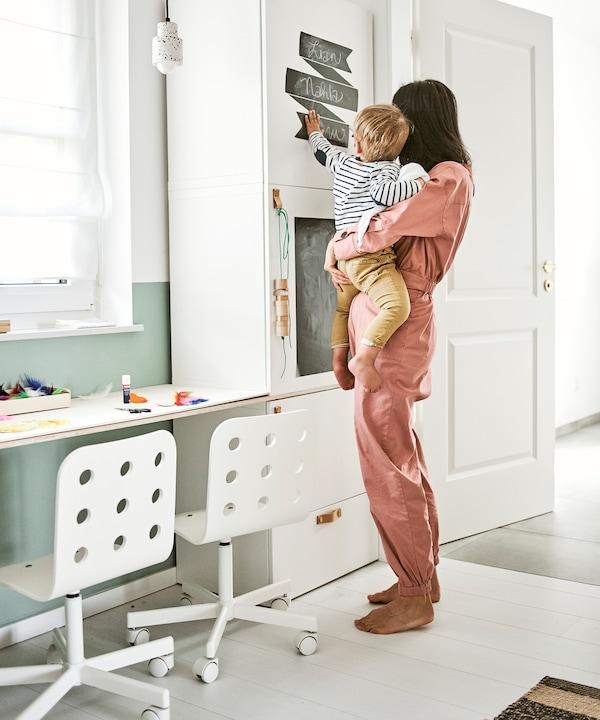 Une femme tient un enfant pointant vers des étiquettes en tableau noir sur une armoire blanche à côté d'un bureau avec deux chaises pour enfants côte à côte.