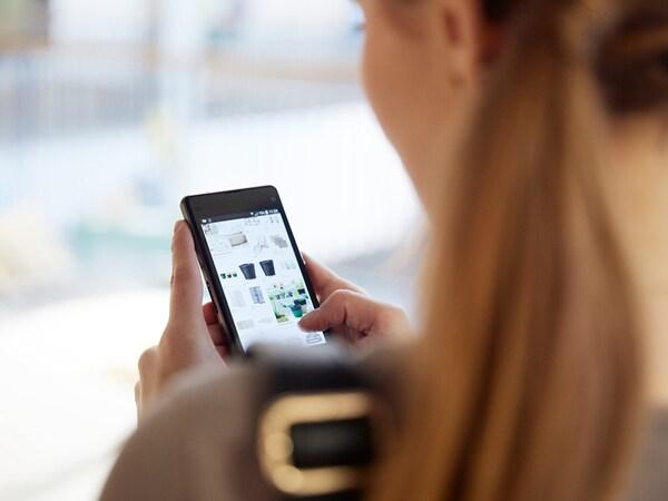 Une femme tient un téléphone intelligent et parcourt le menu à l'écran.