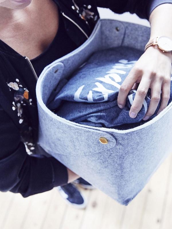 Une femme tient une boîte en tissu dans laquelle se trouvent des t-shirts pliés.