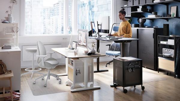 Une femme travaillant à un bureau assis/debout BEKANT, près d'une grande fenêtre. Des tablettes avec des dossiers sont accrochées au mur derrière elle.
