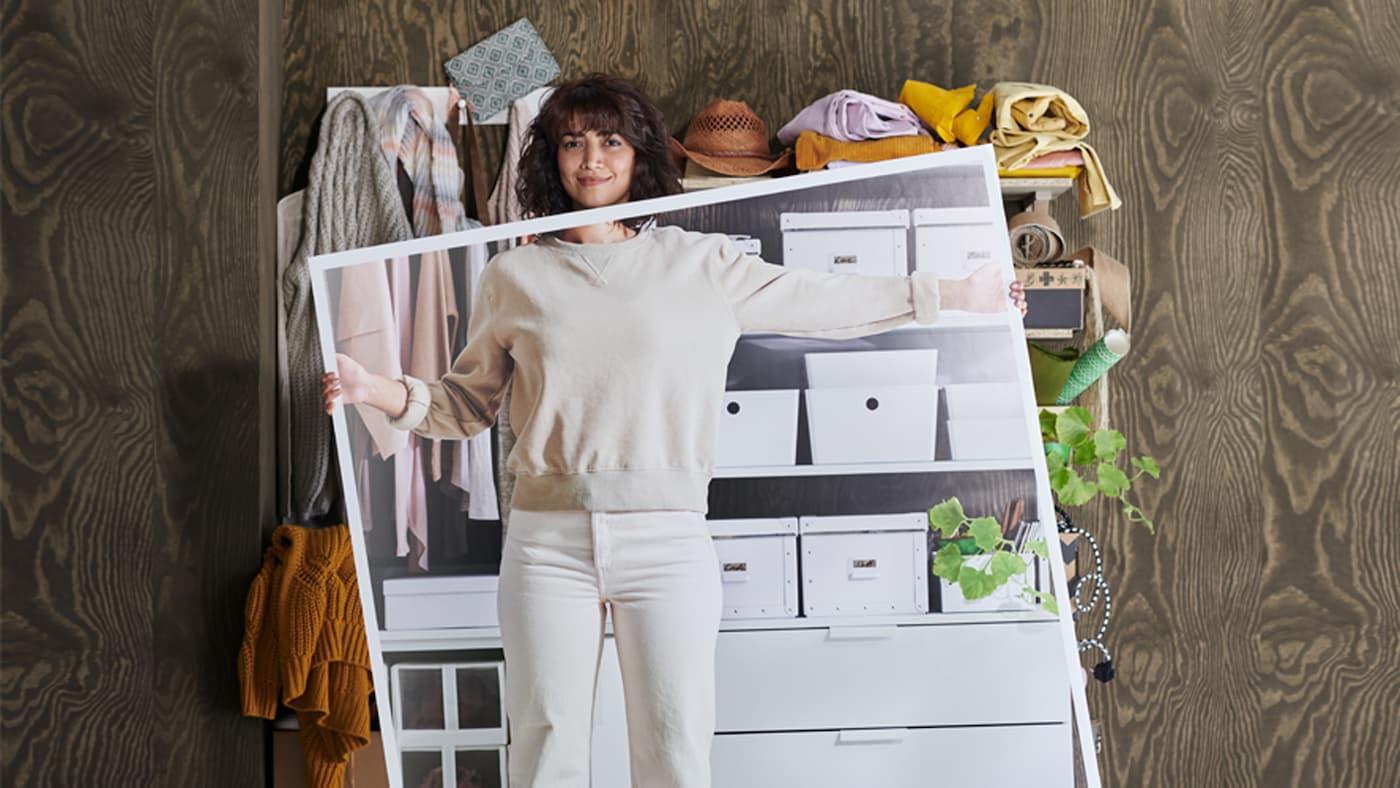 Une femme vêtue de blanc se trouve devant des étagères encombrées, tenant une grande photo de ces mêmes étagères, bien rangées.