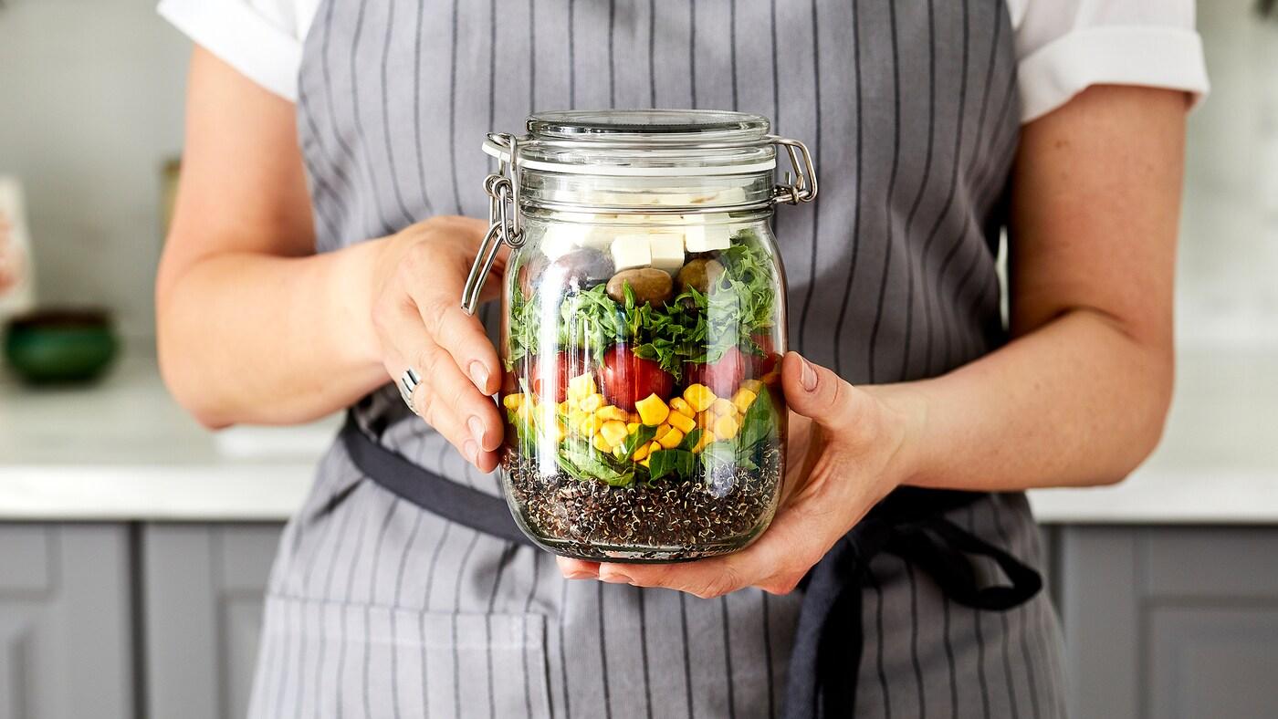 Une femme vêtue d'un tablier est debout dans la cuisine. Elle tient dans ses mains un bocal en verre contenant une salade étagée colorée.