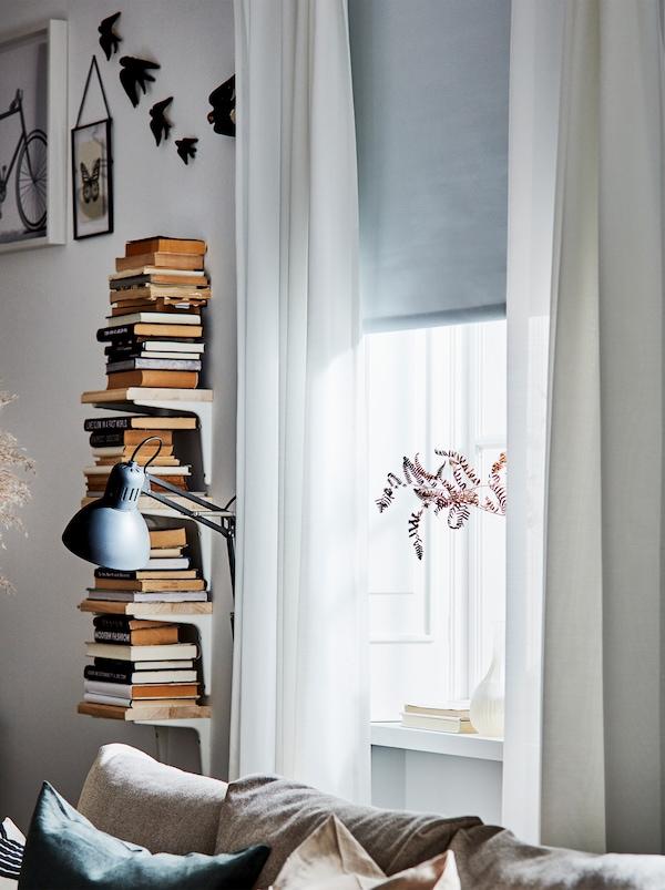 Une fenêtre avec des rideaux semi-transparents blancs, un store gris et un présentoir à livres vertical à côté d'une lampe de lecture.