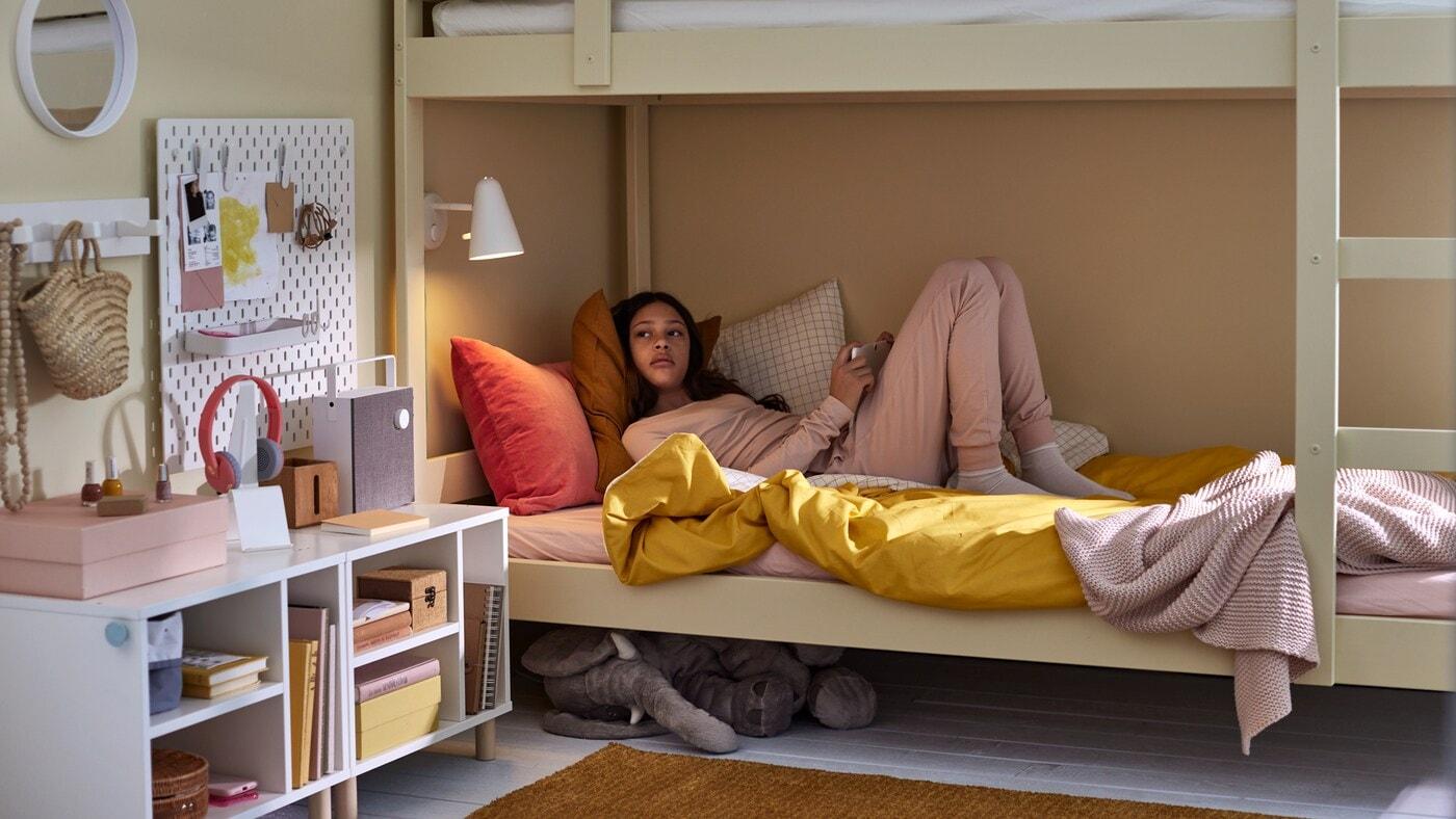 Une fille couchée dans le lit inférieur d'un lit superposé avec un linge de lit de couleurs assorties, un éléphant en peluche sous le lit et du rangement blanc varié.