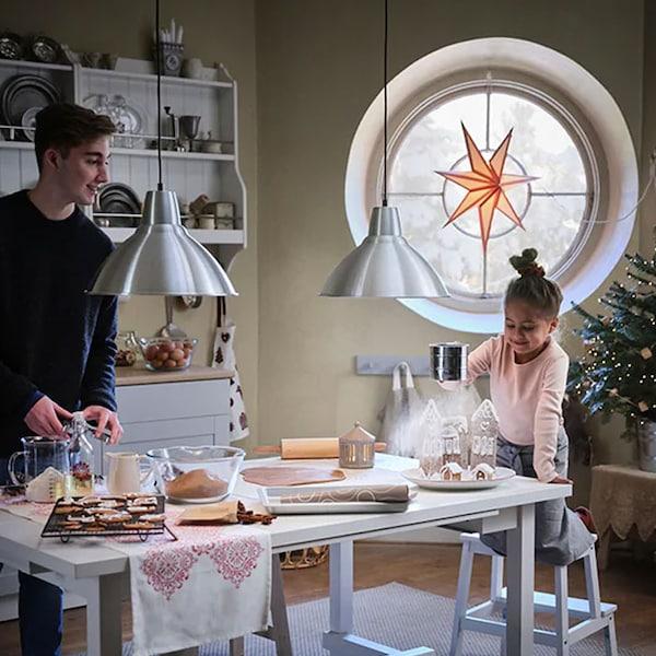 Une fille et un garçon qui cuisinent des douceurs de Noël.