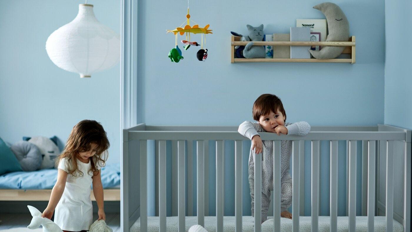 Une fille qui tient deux peluches à côté d'un tout-petit debout dans un lit à barreaux gris, devant un lit pour enfants avec un linge de lit bleu.