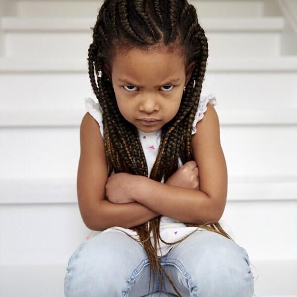 Une fillette assise sur des escaliers blancs qui a les bras croisés et qui boude.