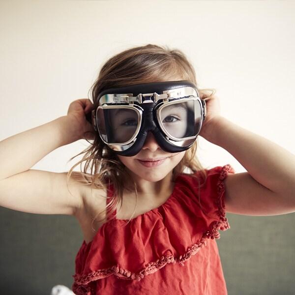 Une fillette avec un haut rouge qui porte de grosses lunettes.