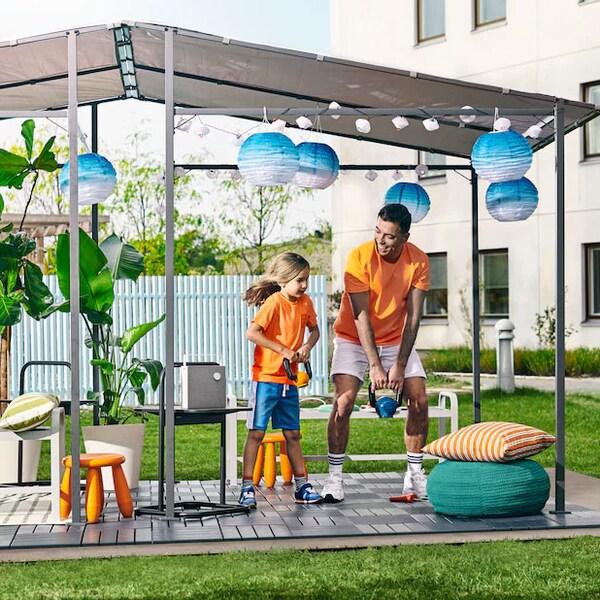 Une fillette et son père soulevant des poids dans un jardin avec une tonnelle GUNNÖN, un plancher en caillebotis RUNNEN et des lampes solaires.