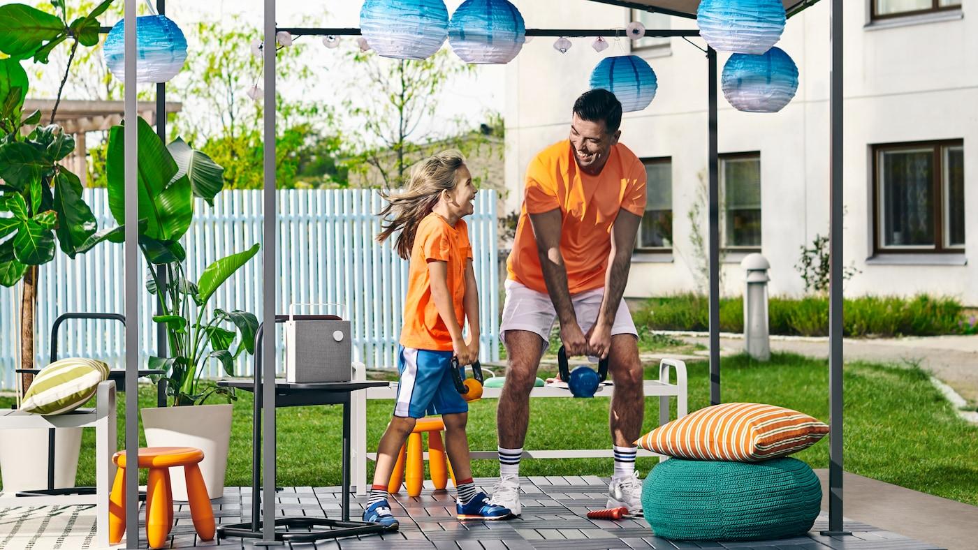 Une fillette et un père soulevant des haltères dans un jardin avec une tonnelle GUNNÖN, des caillebotis d'extérieur RUNNEN et des lampes à énergie solaire.
