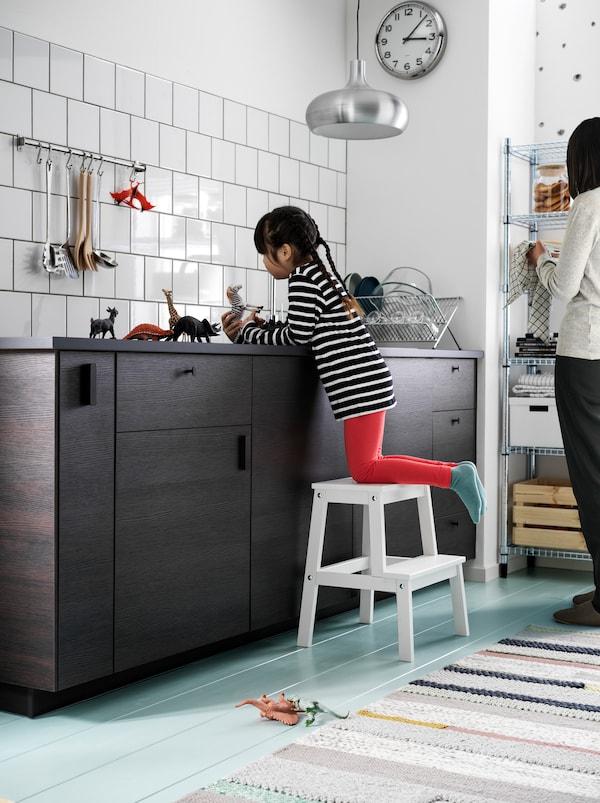 Une fillette, perchée sur un marchepied BEKVÄM, joue avec des animaux-jouets sur un comptoir de cuisine sombre. Une femme se tient à proximité.