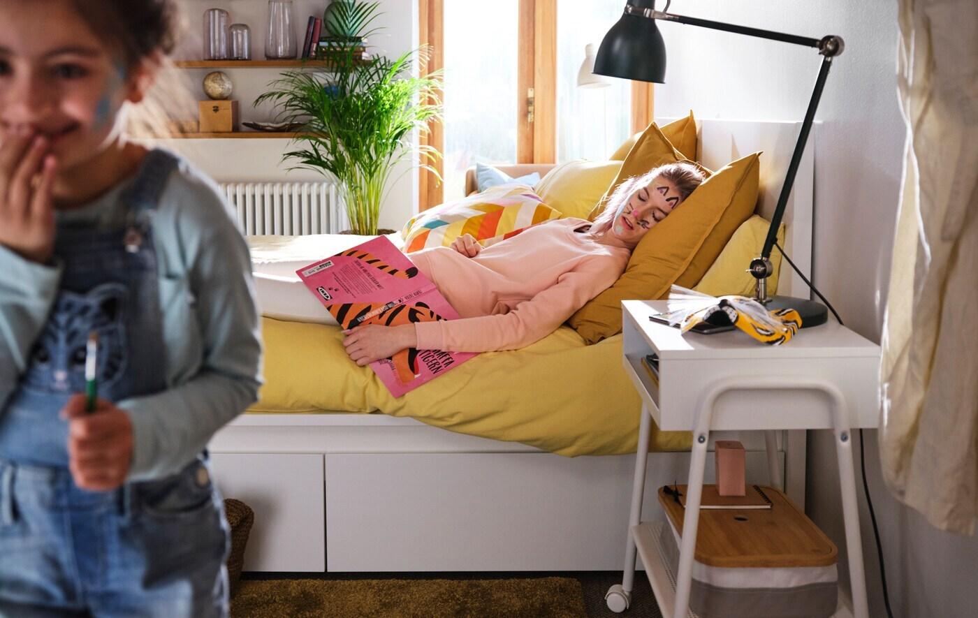 Une fillette sort en douce d'une chambre d'allure moderne après avoir peint des moustaches de chat sur le visage de sa mère, endormie dans un litMALM.