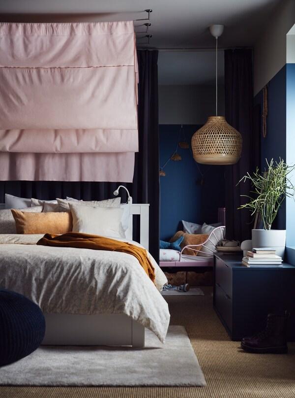 Une grande chambre à coucher avec des murs bleu foncé et un tissu rose au-dessus d'un grand lit double et un lit d'enfant en arrière-plan.