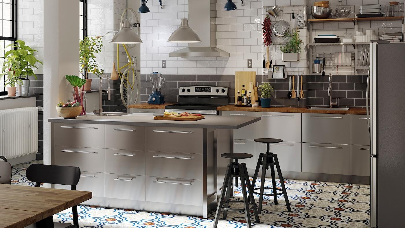 Une grande cuisine avec des façades en inox, des comptoirs en chêne/placage, des suspensions en inox et un îlot.