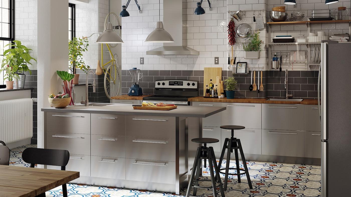 Une grande cuisine avec des portes d'armoires en acier inoxydable, un îlot avec un comptoir à effet de béton et de quartz et deux tabourets de bar noirs.