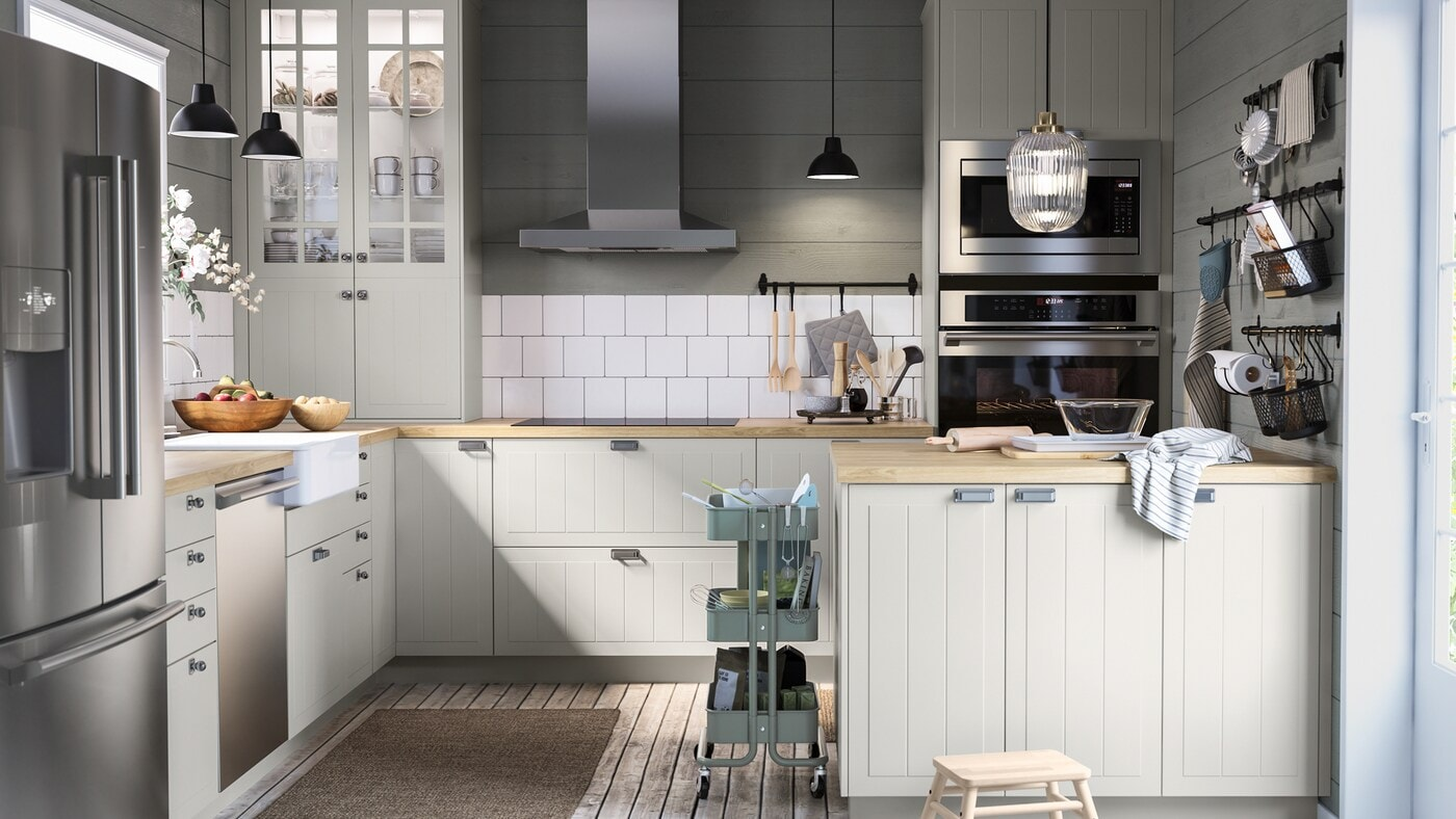 Une grande cuisine vert et blanc, des ustensiles sur un îlot de cuisine, des barres-supports noires munies de crochets et une desserte.