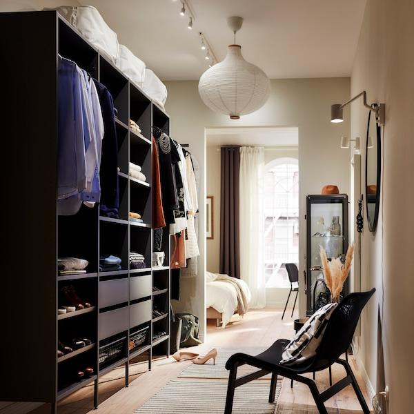 Une grande penderie ouverte en gris foncé avec vêtements pliés sur tablettes, vêtements suspendus sur tringles et quatre tiroirs.