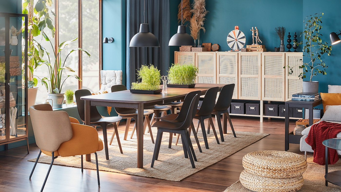 Une grande table brun foncé, huit chaises anthracite, un fauteuil jaune et un rangement modulaire avec portes en bambou.