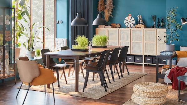 Une grande table brun foncé, huit chaises anthracite, un fauteuil jaune et un système de rangement aux portes en bambou.