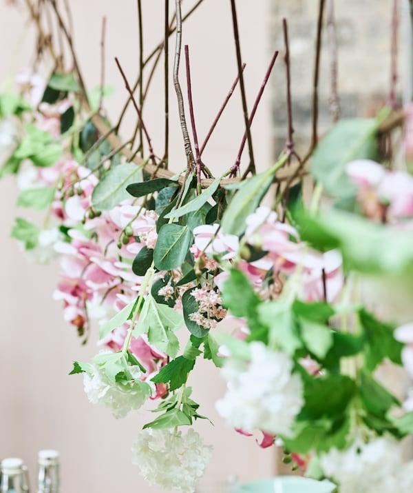Une guirlande estivale fabriquée avec des fleurs artificielles roses et blanches suspendues à une corde à linge.