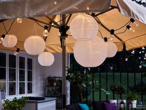 Une guirlande lumineuse de couleur noire et des suspensions rondes sous un parasol ouvert, pour une lumière chaleureuse et cosy.