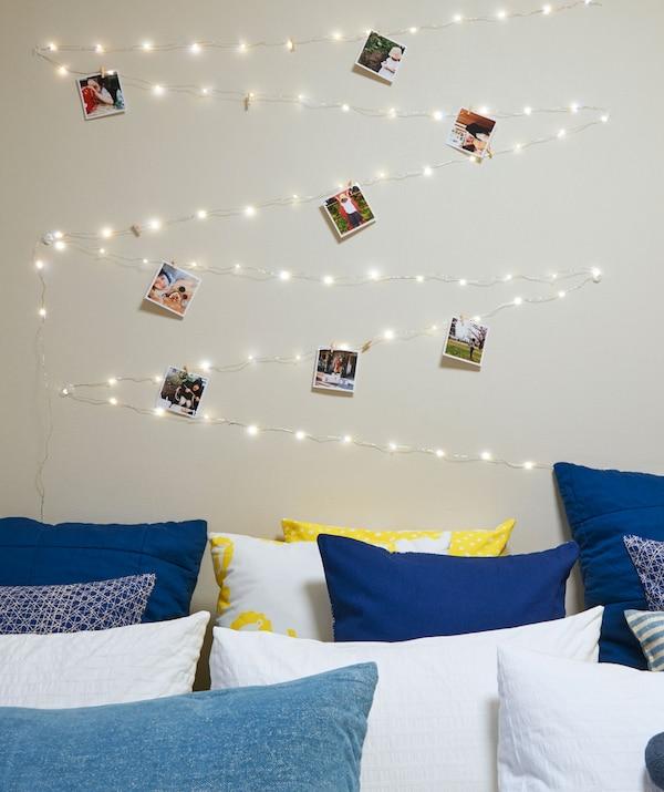 Une guirlande lumineuse où sont accrochées des photos, disposée en zigzag sur le mur au-dessus d'un lit couvert de coussins.