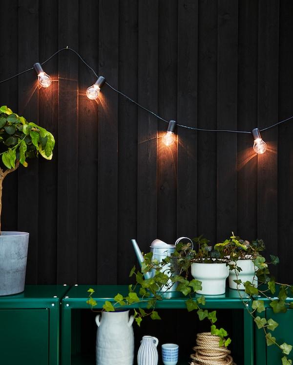 Une guirlande lumineuse SVARTRÅ LED accrochée au mur éclaire la terrasse d'une douce lumière.