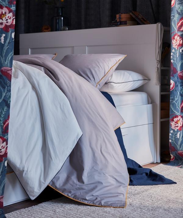 Une housse de couette grise aux bords jaunes IKEA KUNGSBLOMMA posée sur un lit bien fourni.