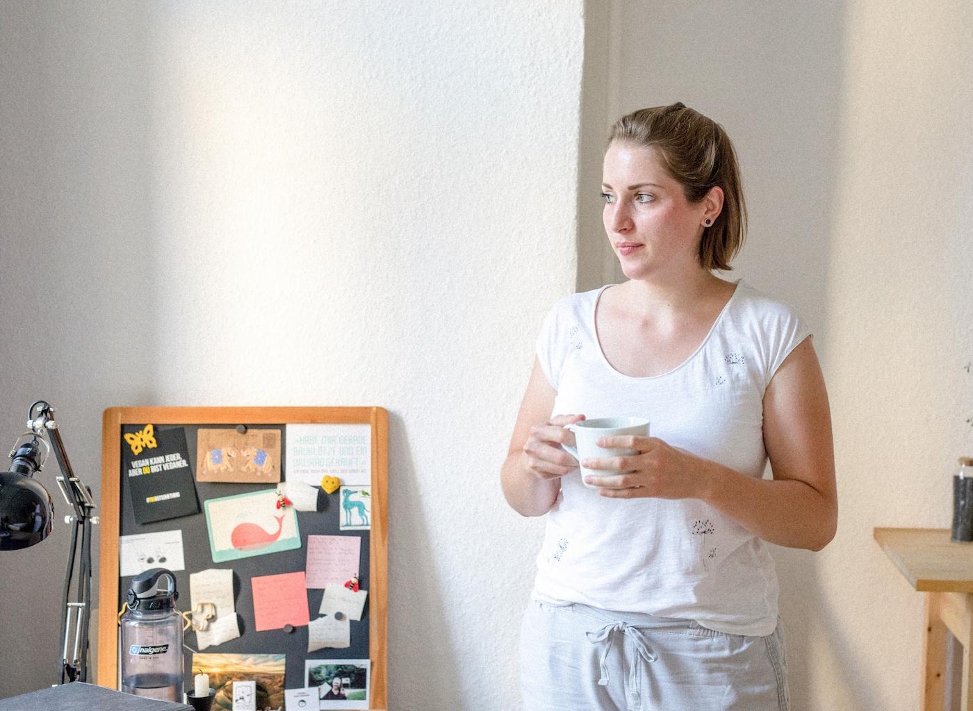 Une jeune femme chez elle, une tasse de thé à la main, qui regarde par la fenêtre.