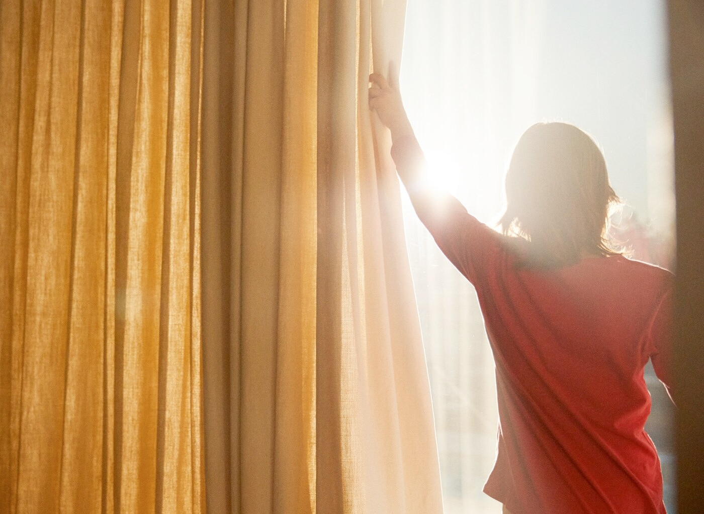 Une jeune femme portant un t-shirt rouge et ouvrant un rideau jaune pour laisser entrer le soleil depuis son balcon.