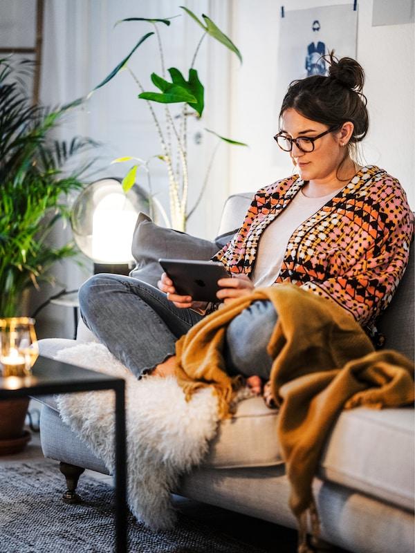 Une jeune fille avec les cheveux relevés est assise en tailleur et lit un livre sur un canapé avec une couverture orange et une peau de mouton.