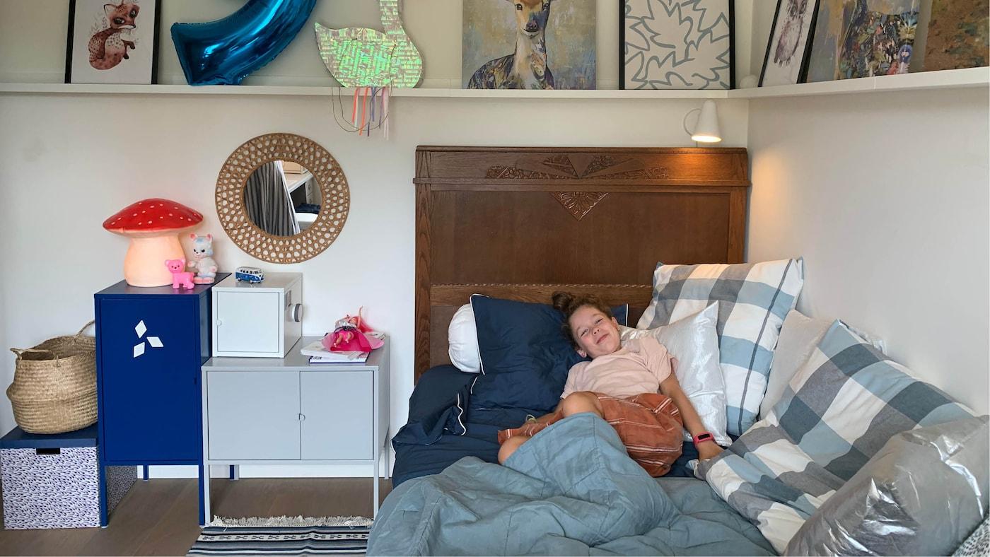 Une jeune fille est allongée au milieu de nombreux coussins bleus dans un lit ancien, surplombé de tablettes pour photos et flanqué de petits éléments de rangement colorés.