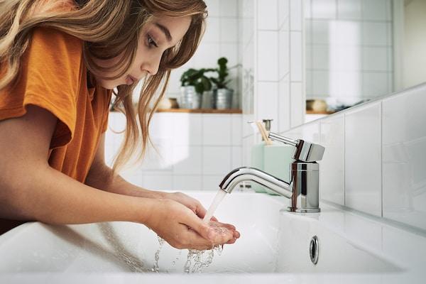 Une jeune fille portant un t-shirt buvant l'eau du robinet de la salle de bain.