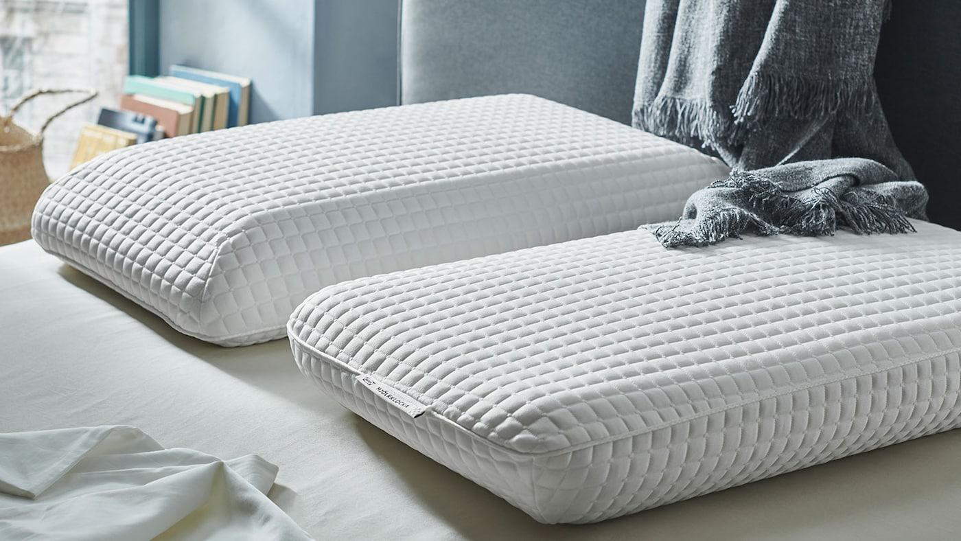 Une jeune homme, couché sur le côté, dort profondément sur un oreiller ergonomique IKEA PRAKTVÄDD.