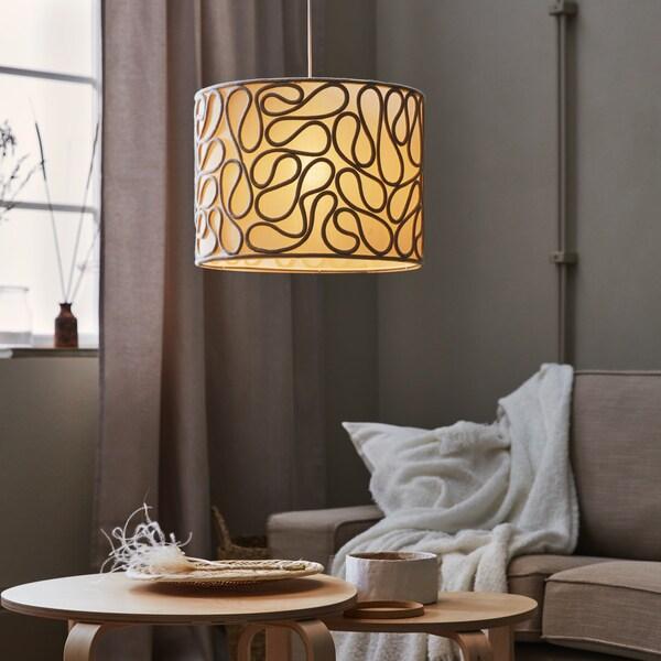 Une lampe à suspension avec motif de fil de fer au-dessus d'une table basse dans un intérieur beige