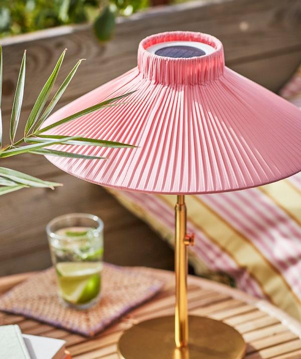 Une lampe de table à énergie solaire SOLVINDEN, éclairée par le soleil, posée sur une petite table, à côté d'un verre contenant une boisson et des rondelles de citron.