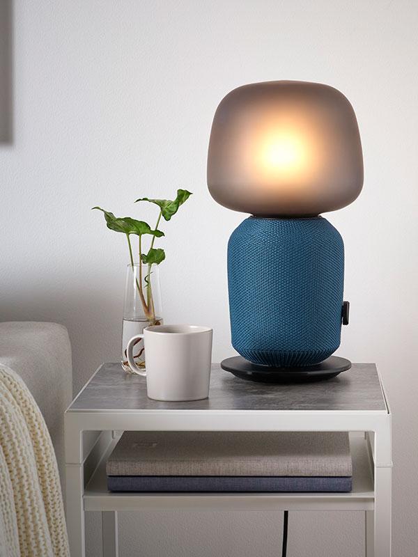 Une lampe de table haut-parleur SYMFONISK allumée munie d'une housse bleue.