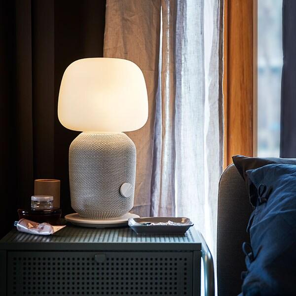 Une lampe de table SYMFONISK allumée sur une table de chevet.