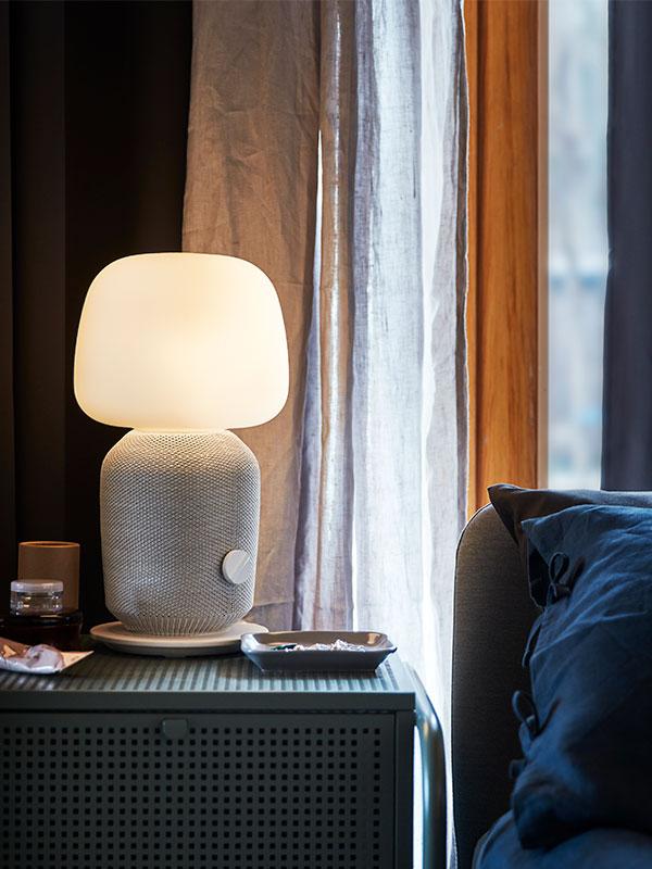 Une lampe de table SYMFONISK sur une table de chevet